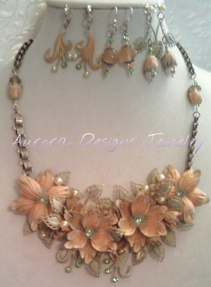 "Beautiful peach and sage green assemblage with three pair of matching earrings.  This piece is at the top of my pyramid.  It's called ""Point, Counterpoint""."