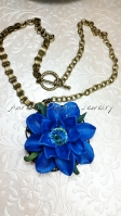 Large blue polymer clay flower with a Swarovski rivoli center, and brass ox book chain.