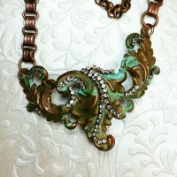This altered piece had been on my work table for over a year. Rhinestone chain accent and book chain finished it.