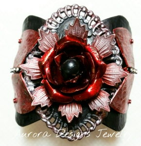 Matte black and Glossy red with a black pearl center and rhinestone cup chain accent. Pearl Ex powder on the focal swirled edges and the outside flower petals.